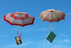 two umbrellas with books hanging off the handle