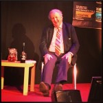 alexander mccall smith sitting in a chair on stage